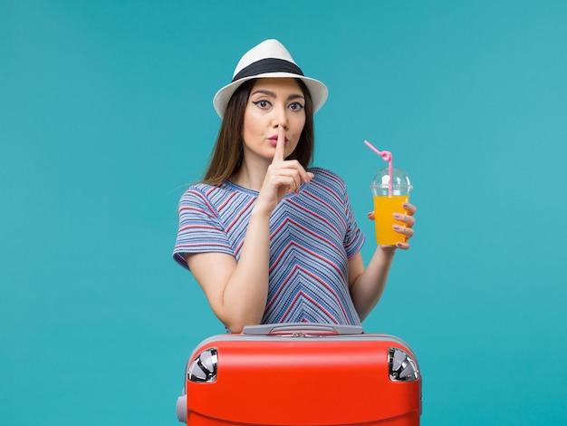 Donna di vista frontale in vacanza con la sua borsa rossa che tiene il suo succo sulla femmina di vacanza viaggio viaggio viaggio viaggio scrivania blu