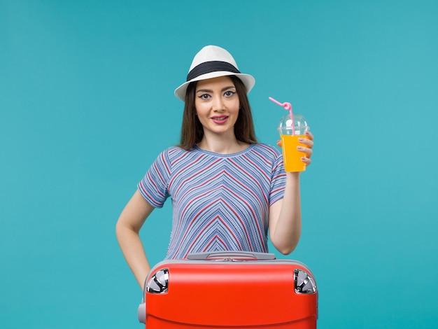 Donna di vista frontale in vacanza con la sua borsa rossa che tiene il suo succo sulla vacanza di viaggio di viaggio di viaggio di estate di viaggio dello scrittorio blu