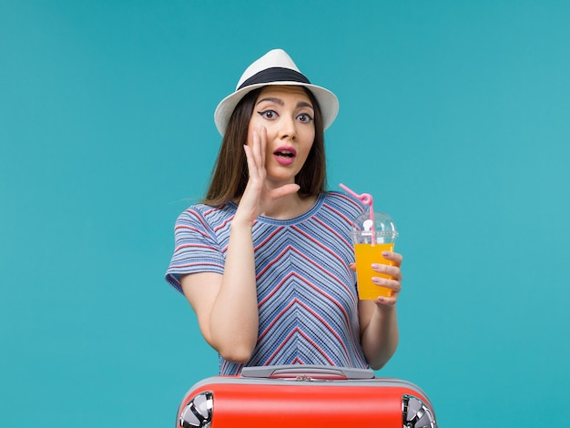 Front view woman in vacation with her red bag holding her juice on light-blue background trip journey voyage vacation female