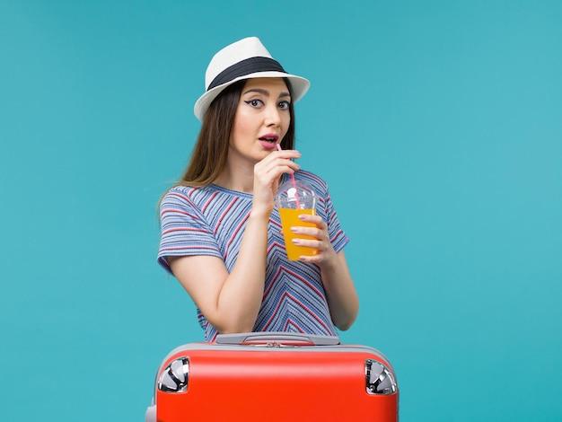 Donna di vista frontale in vacanza con la sua borsa rossa che tiene il suo succo su sfondo azzurro viaggio viaggio viaggio vacanza femminile