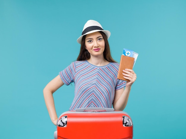 Donna di vista frontale in vacanza con la sua borsa rossa che tiene i biglietti su sfondo blu biglietto di viaggio viaggio viaggio vacanza femminile