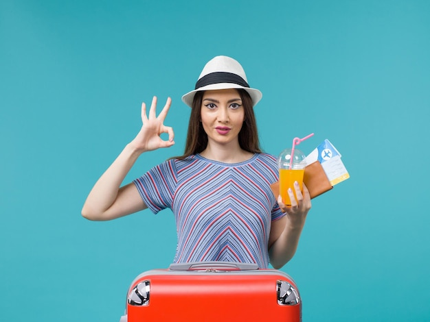 Donna di vista frontale in vacanza con la sua borsa rossa che tiene i biglietti e il succo su una femmina di vacanza di viaggio viaggio viaggio sfondo blu