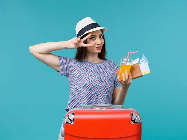 Donna di vista frontale in vacanza con la sua borsa rossa che tiene i biglietti e il succo su un viaggio femminile di vacanza di viaggio di viaggio di sfondo blu