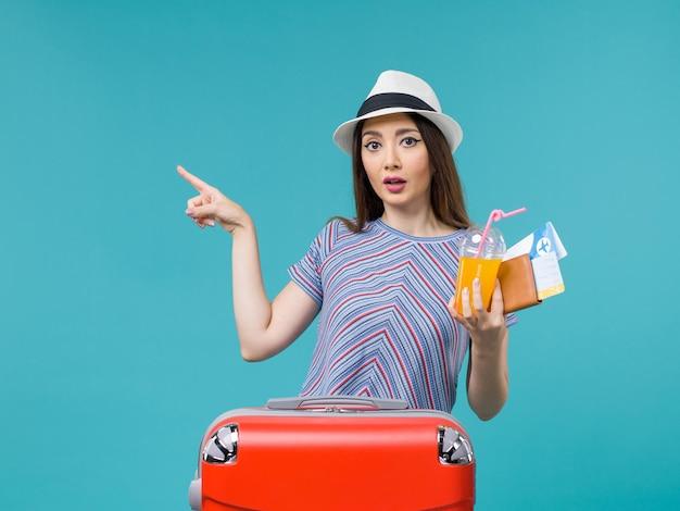 Donna di vista frontale in vacanza con la sua borsa rossa che tiene i biglietti e il succo sul viaggio femminile di vacanza di viaggio di viaggio dello scrittorio blu
