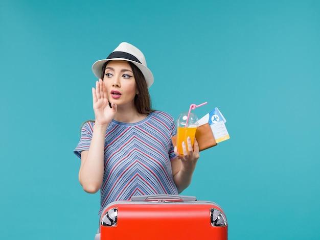 Donna di vista frontale in vacanza con la sua borsa rossa che tiene i biglietti e il succo sul viaggio femminile di viaggio di viaggio di viaggio del pavimento blu