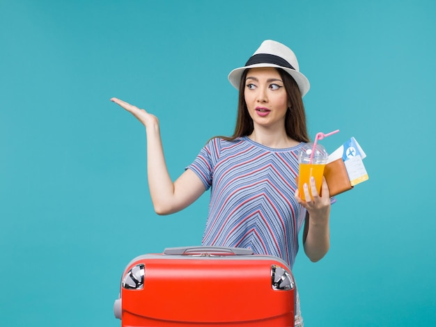 Front view woman in vacation with her red bag holding tickets and juice on light-blue background journey trip voyage vacation female