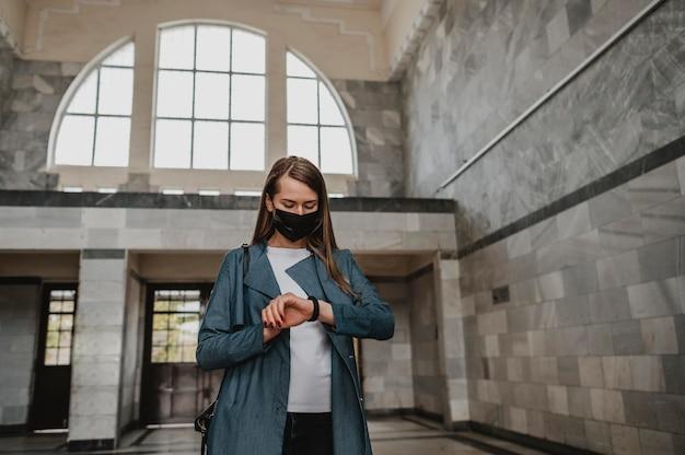 駅の屋内で待っている正面図の女性