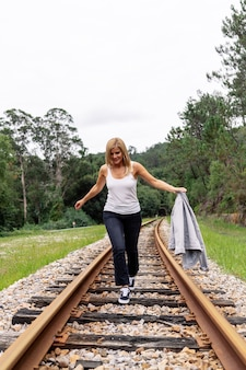 Front view of a woman walking along a train track with greenery