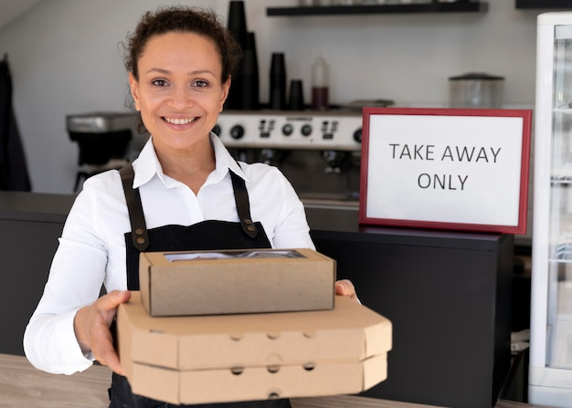 Front view of woman wearing apron holding packed takeaway food Premium Photo