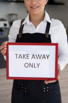 Front view of woman wearing apron holding sign with takeaway only Premium Photo