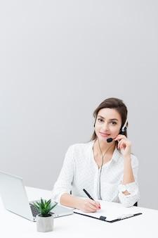 Front view of woman wearing headset and working at desk with laptop