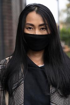 マスクを身に着けている正面図の女性
