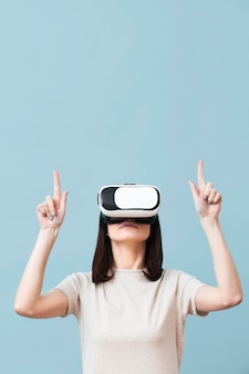 Front view of woman wearing virtual reality headset and pointing up