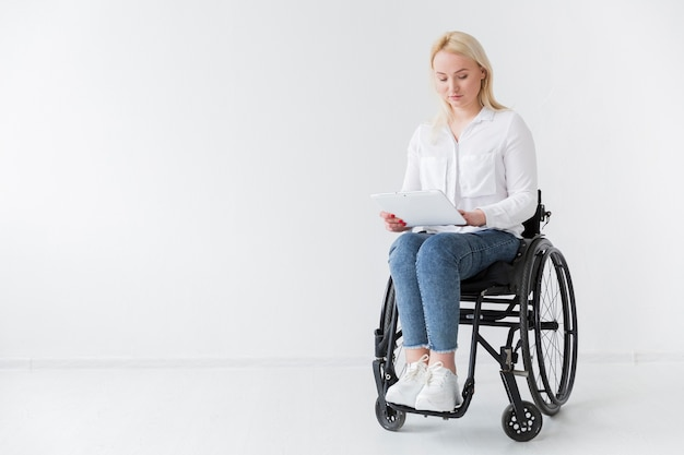 Front view of woman in wheelchair holding tablet