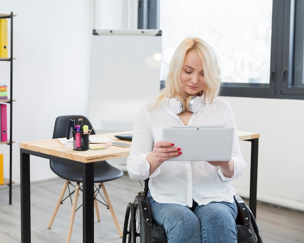 Front view of woman in wheelchair at the office holding tablet