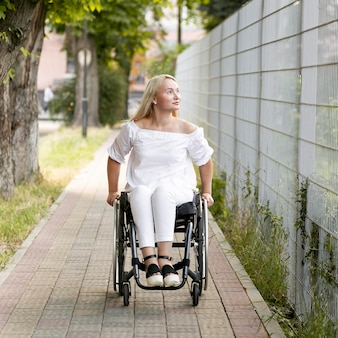 Front view of woman in wheelchair outdoors