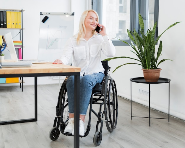 Front view of woman in wheelchair talking on phone at work
