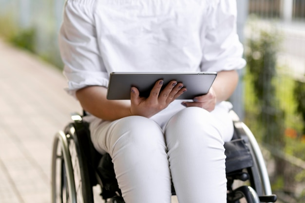 Front view of woman in wheelchair with tablet