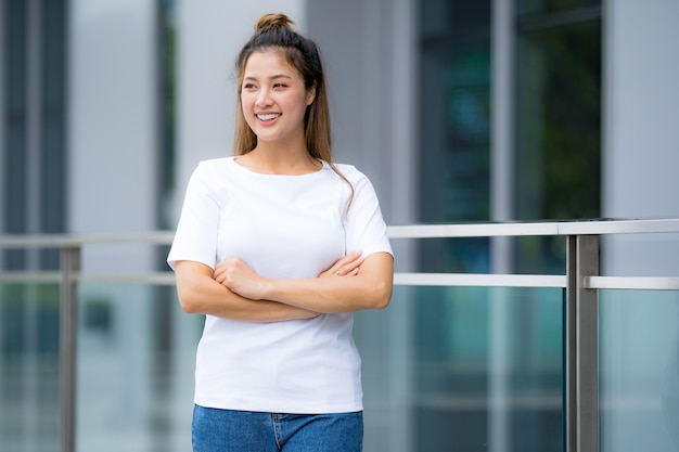 Front view, woman in white t-shirt and blue jeans, standing outside in the city street