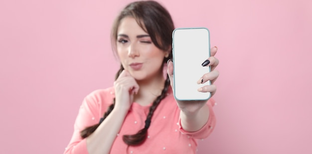 Front view of woman winking and holding up smartphone