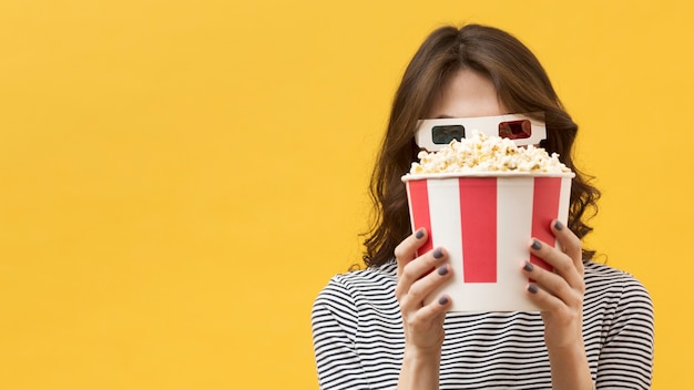 Front view woman with 3d glasses covering her face with a popcorn bucket