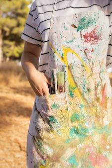 Vista frontale della donna con il grembiule pieno di vernice