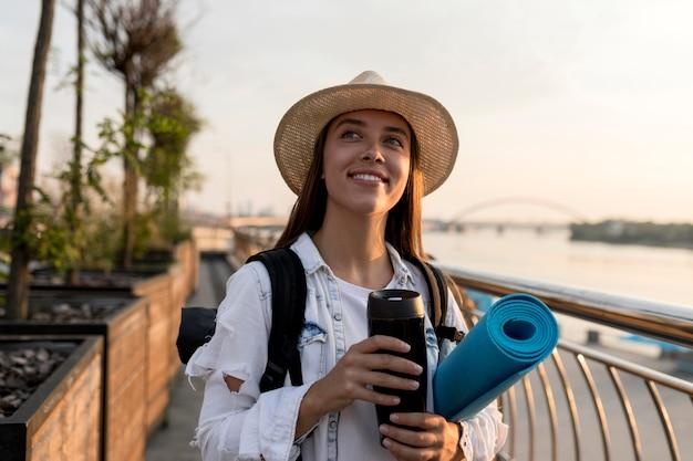 Vista frontale della donna con zaino e cappello tenendo il thermos durante il viaggio