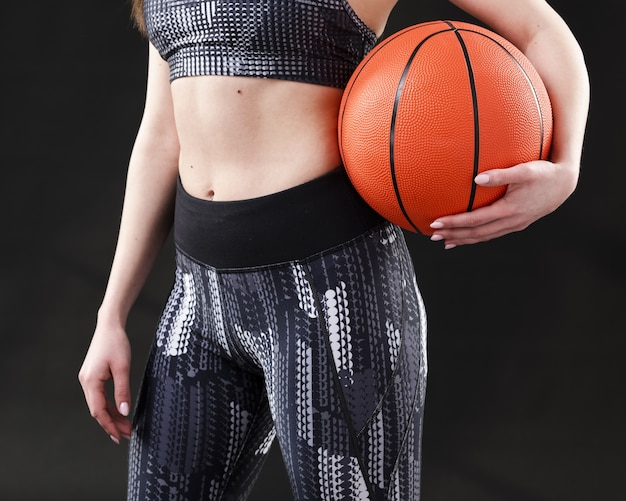Front view of woman with basketball ball