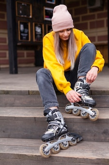Front view of woman with beanie looking at roller blades