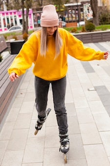 Front view of woman  with beanie rollerblading