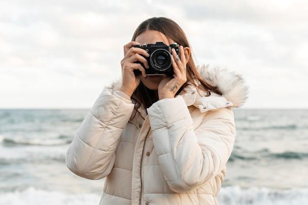 Vista frontale della donna con la macchina fotografica in spiaggia
