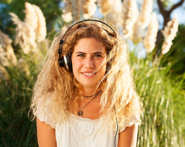 Front view of woman with curly hair listening to music