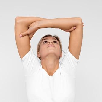 Vista frontale della donna con fare fisioterapia sollevando le braccia