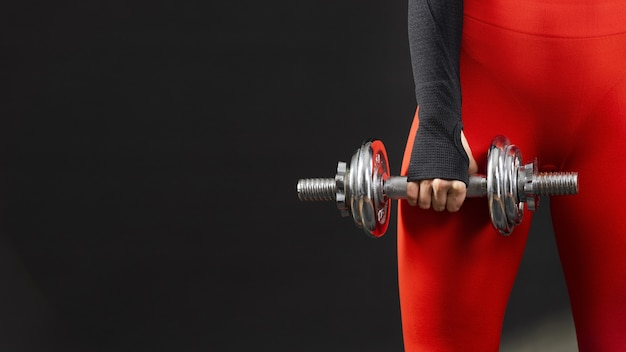 Front view of woman with dumbbells and copy space