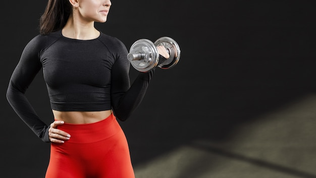Front view of woman withdumbbells and copy space