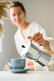 Front view of woman with eye patches pouring coffee