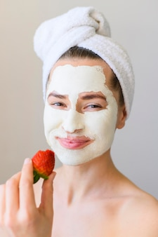 Front view of woman with face mask holding strawberry
