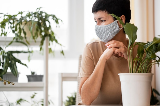 Front view of woman with face mask posing next to indoor plant with copy space
