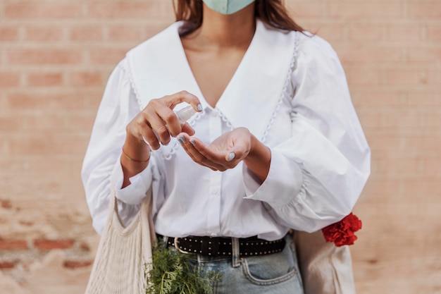 Front view of woman with face mask using hand sanitizer