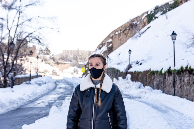 Front view of a woman with a face mask walking on a snowy city avenue.