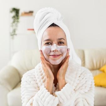 バスローブを着ている顔のマスクを持つ正面女性