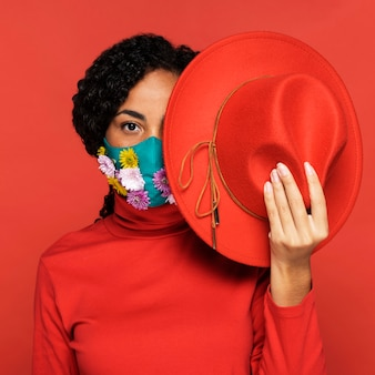 Front view of woman with flowers on her mask posing with hat