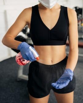 Vista frontale della donna con guanti e mascherina medica in palestra utilizzando un disinfettante