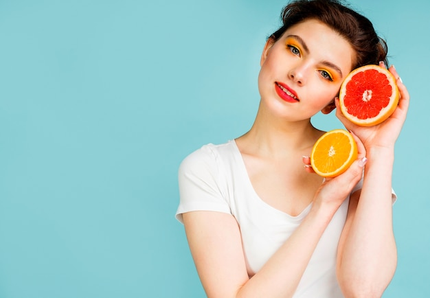 Front view of woman with grapefruit and orange