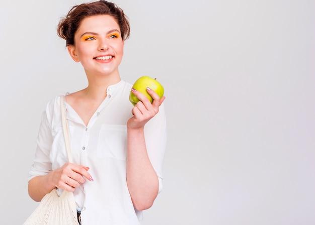 Vista frontale della donna con la mela verde