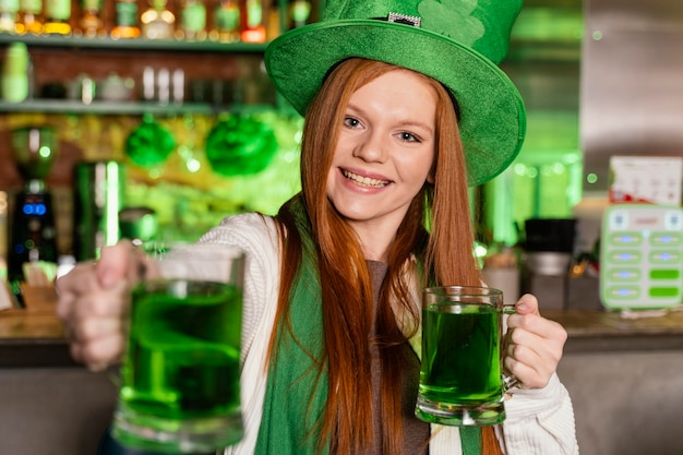 Front view of woman with hat celebrating st. patrick's day at the bar with drinks