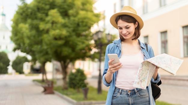 Женщина вид спереди в шляпе, проверка мобильного телефона