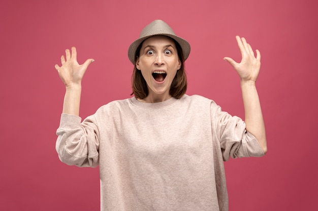 Front view of woman with hat posing shocked