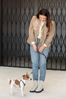 Front view of woman with her dog wearing a leash
