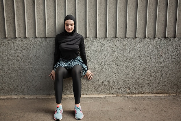 Front view of woman with hijab exercising